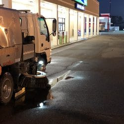 Street sweeping in retail parking lot with truck